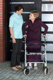 Nurse helping senior woman with walker Stock Image