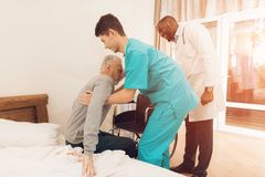 The nurse helps the elderly man to get out of bed and sit in a wheelchair. stock photos