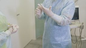 Nurse helps a surgeon to put on sterile gloves before sclerotherapy surgery in hospital. Concept of phlebology stock footage