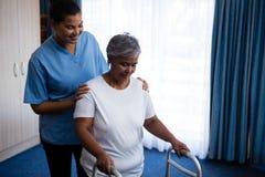 Nurse hepling senior woman in walking with walker stock images