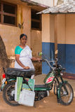 Nurse and her motorbike serving rural communities. Dindigul, India - October 22, 2013: A public funded nurse swings by preschool to inoculate a kid with a polio Royalty Free Stock Photos