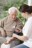 Nurse holding blood pressure gauge Royalty Free Stock Images