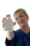 Nurse holding bottle of pills with blank label. Photo of nurse with stethoscope holding bottle of pills with blank label in front of her; focus is on bottle of royalty free stock photo