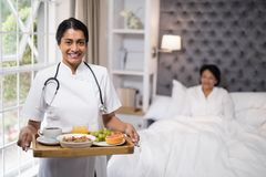 Nurse holding breakfast tray while patient lying on bed at home Royalty Free Stock Image