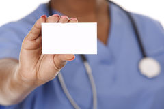 Nurse holding business card. Black nurse wearing scrubs on white isolated background Stock Photos