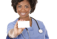 Nurse holding business card. Black nurse wearing scrubs on white isolated background Royalty Free Stock Images