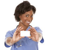 Nurse holding business card. Black nurse wearing scrubs on white isolated background Stock Image