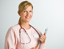 Nurse holding clipboard. Nurse holding a clipboard and smiling Stock Photo
