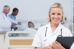 Nurse holding clipboard and looking at the camera Stock Image