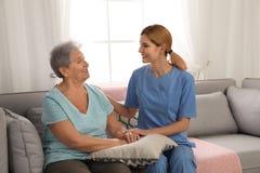Nurse holding elderly woman`s hands. Assisting senior people stock photo