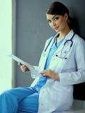 Nurse holding folder and taking notes - sitting Stock Photo