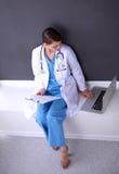 Nurse holding folder and taking notes - sitting Stock Photos