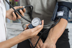 Nurse Holding Gauge While Measuring Blood Pressure Of Patient. Midsection of female nurse holding gauge while measuring blood pressure of patient in pharmacy stock image
