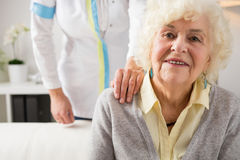 Nurse holding hand on elderly womans shoulder Royalty Free Stock Image