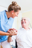 Nurse holding hand of senior man in rest home. Nurse holding hand of senior men in rest home Royalty Free Stock Photo