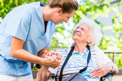 Nurse holding hand of senior woman in pension home Stock Images