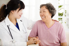 Nurse holding hand of senior woman in rest home. Nurse holding hand of asian senior women in rest home Stock Photo