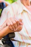 Nurse holding hand of senior woman in wheel chair Stock Image