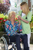 Nurse Holding Hands with Senior Woman in Garden Royalty Free Stock Photos