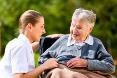 Nurse holding hands with senior woman in wheelchair Stock Photography