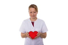 Nurse holding an heart in her hands. Nurse holding a red heart Royalty Free Stock Image