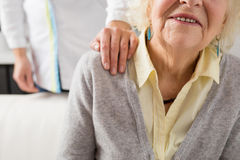 Nurse holding her hand on seniors shoulder Stock Images