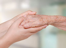 Nurse holding old patient hand. Young nurse holding old patient hand in hospital Royalty Free Stock Photo