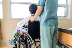 Nurse Holding Patient's Wheelchair's Handle By Stock Photo