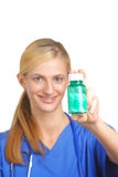 Nurse holding pills with focus on bottle. Nurse holding pills in scrubs with focus on bottle Stock Image