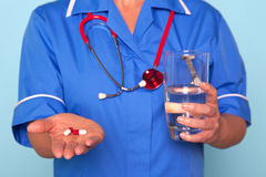 Nurse holding pills and a glass of water Stock Photos