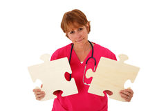 Nurse Holding Puzzle Pieces. Nurse In Her 50's Holding Two Connecting Puzzle Pieces Stock Photos