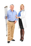 Nurse holding a senior patient with crutches. Full length portrait of a female doctor or nurse holding a senior patient with crutches  on white background Royalty Free Stock Images