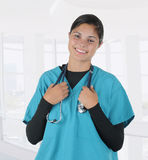 Nurse Holding Stethoscope in Modern Clinic Setting. A young nurse or medical student holding a stethoscope that is draped around her neck. The woman is standing Stock Image