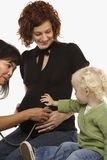 Nurse holding stethoscope on pregnant woman's belly. Stock Photo