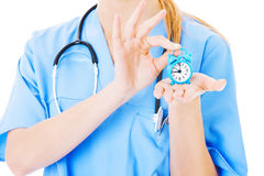 Nurse Holding Toy Alarm Clock Over White Background Royalty Free Stock Photography
