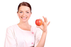 Nurse holding up an apple Stock Images