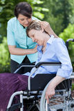 Nurse hugging woman on a wheelchair Stock Images