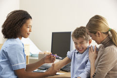 Nurse injecting child with mother Royalty Free Stock Images
