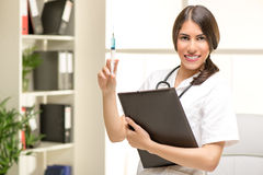 Nurse With Injection. Young cute female doctor in a white coat, with a stethoscope over the neck holding an injection and folder, with a smile looking at the Royalty Free Stock Photo
