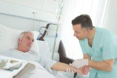 Nurse inserting needle into arm senior male hospital patient. Nurse inserting needle into arm of senior male hospital patient Royalty Free Stock Images