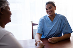 Nurse interacting with senior woman in retirement home. Nurse interacting with senior women at table in retirement home Stock Photo