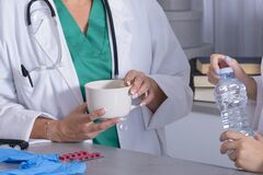 Nurse keeping a water bottle and a female doctor keep cup of coffee