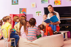 Nurse in kindergarten read book to the class. Large group of kids sit and listen to teacher reading a book and telling stories Royalty Free Stock Photos