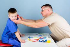 Nurse laboratory assistant. family doctor. small boy with dad play. Future career. happy child with father with royalty free stock images