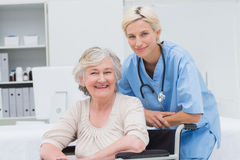 Nurse leaning on senior patients wheelchair at clinic Stock Images