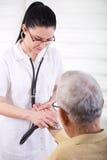 Nurse listening hearbeat of old man Royalty Free Stock Image