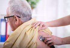 Nurse  listening heartbeat of old man Royalty Free Stock Image