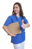Nurse with long dark hair and file showing thumb up Royalty Free Stock Image