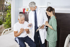 Nurse Looking At Doctor Explaining Prescription To Patient royalty free stock images
