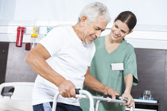 Nurse Looking At Patient Using Walker In Rehab Center Stock Images